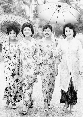 28 March 1960: The drizzle on Hari Raya morning did not prevent these four charming Malay girls in Kampong Baru, Kuala Lumpur from visiting their friends and exchanging greetings. The girls from left to right are: Rohani Mohamed, Nora Abu Hassan, Zainun Mohamed and Jasmin A. Hassan. FOR SUNDAY TIMES